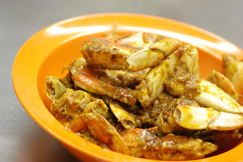 Chili crab in a typical Malaysian orange plastic bowl