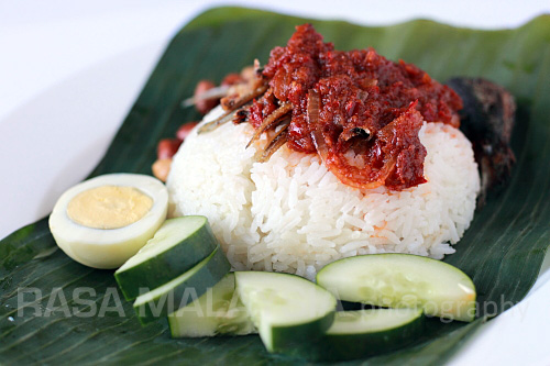 Close up of nasi lemak on a banana leaf with fried crispy anchovies, toasted peanuts, fried fish, sambal and cucumber.