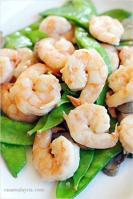 Stir fry shrimps with snow peas and brown Asian sauce.