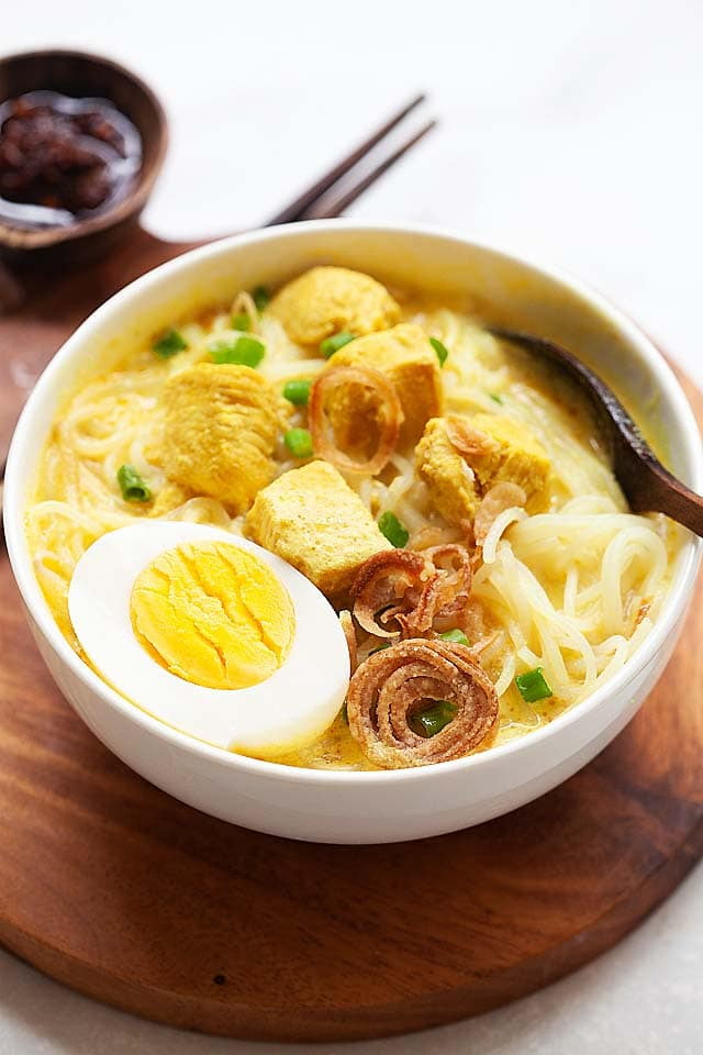 Soto ayam recipe with chicken and spices in a soup.