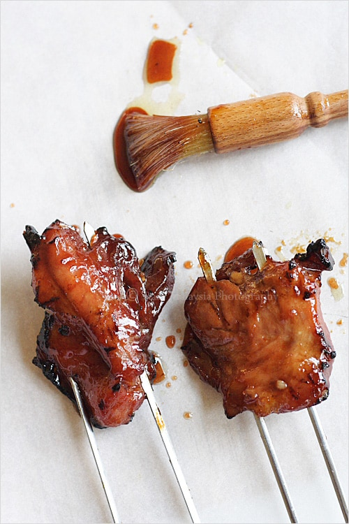 Chinese BBQ pork on skewers slathered in char siu or char siew sauce next to basting brush