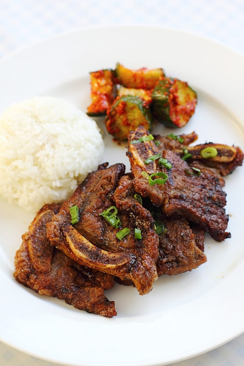 Delicious kalbi or Korean short ribs on a plate with rice and spicy cucumber salad. Try this recipe at home today.