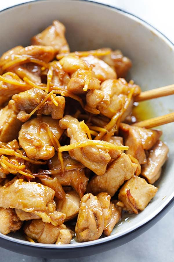 Easy homemade Asian sesame oil chicken with a pair of chopsticks.