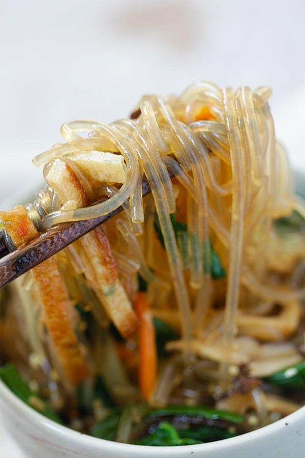 Japchae Korean noodle picked with a pair of chopsticks.