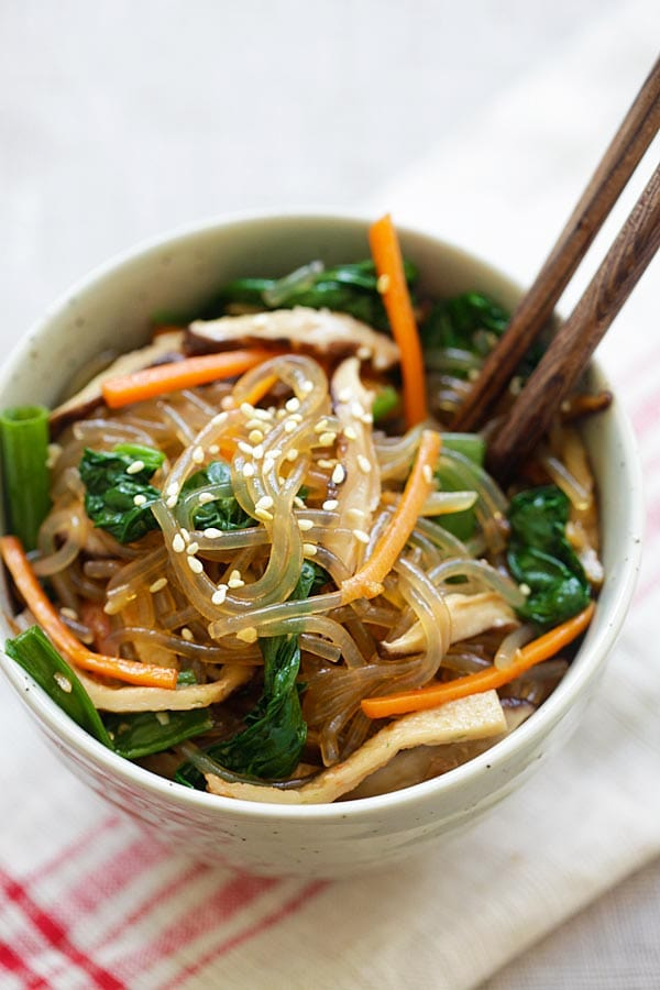 Korean Japchae with sweet potato noodles and vegetables in a bowl with a pair of wooden chopsticks.