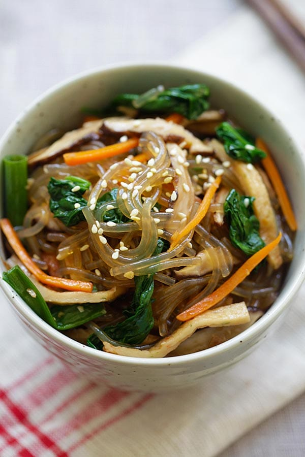 Korean glass noodle dish with sweet potato noodles and vegetables topped with sesame seeds in a bowl.