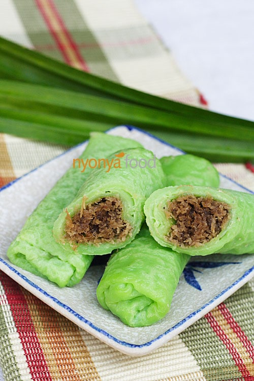 Kuih dadar or kuih tayap is a rolled crepe flavored with pandan juice and filled with grated coconut steeped in gula melaka or Malaysian palm sugar.   rasamalaysia.com