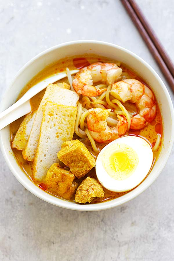 Spicy street food laksa noodle dish from Malaysia and Singapore, served in a bowl, topped with boiled eggs, tao pok, shrimps and sliced fish cakes.