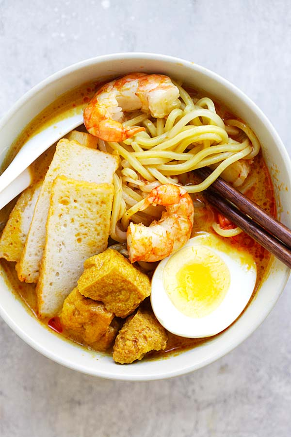 Laksa - Spicy street food noodle dish popular in Malaysia and Singapore. This homemade curry laksa recipe is so easy and delicious | rasamalaysia.com