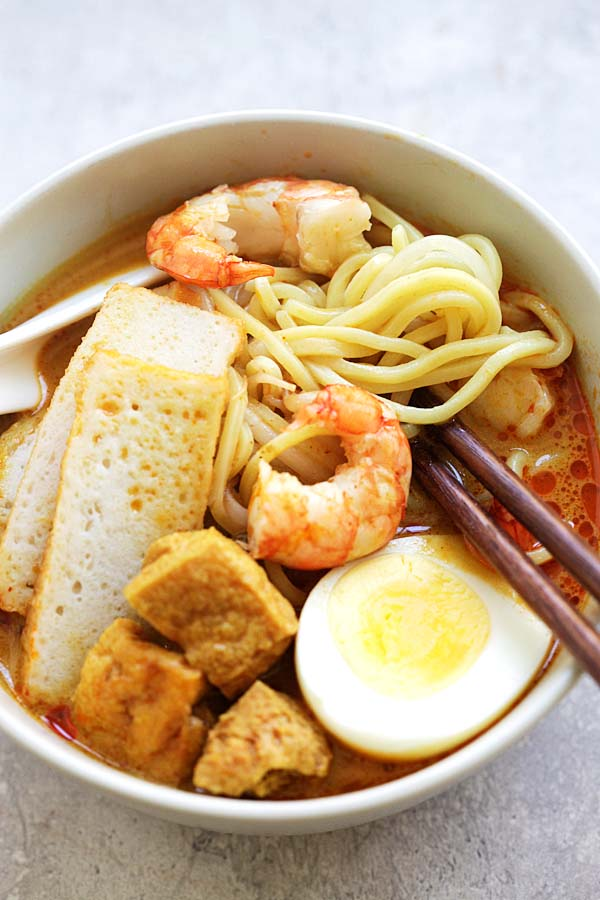 Curry Laksa in a bowl, with a pair of chopsticks picking the noodles.