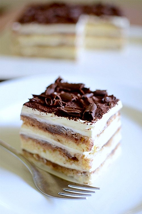 Easy and quick homemade heavenly eggless tiramisu cake served in a plate with a fork.