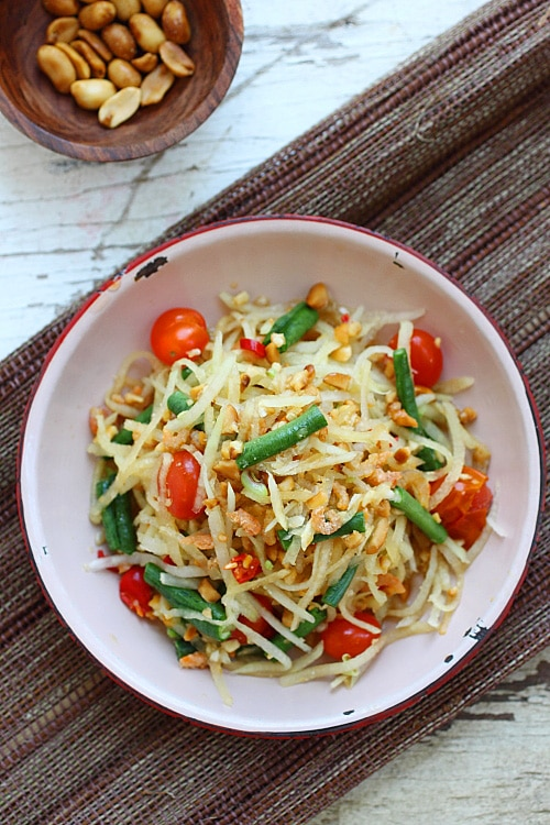 Top down view of low calorie Thai Green Papaya Salad in a plate ready to serve with peanuts, green beans, and tomatoes.