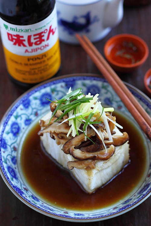 Chinese steamed fish in dark sauce topped with mushrooms and ginger.