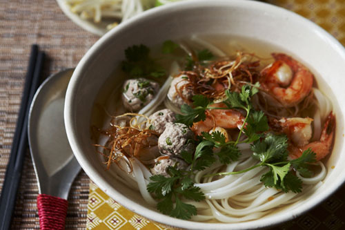 Homemade Phnom Penh noodle soup recipe with lime wedges and extra bean sprouts on the side, ready to serve.