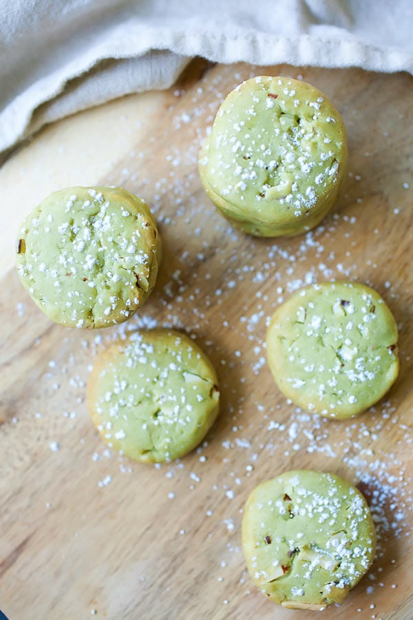 Top down view of easy homemade Japanese matcha cookies with almond dusted with powdered sugar.