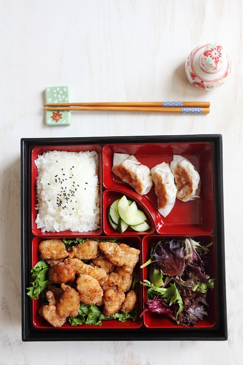Japanese Fried Chicken Bento with steamed rice and sesame seeds, pickled cucumbers, salad and Gyoza. | rasamalaysia.com