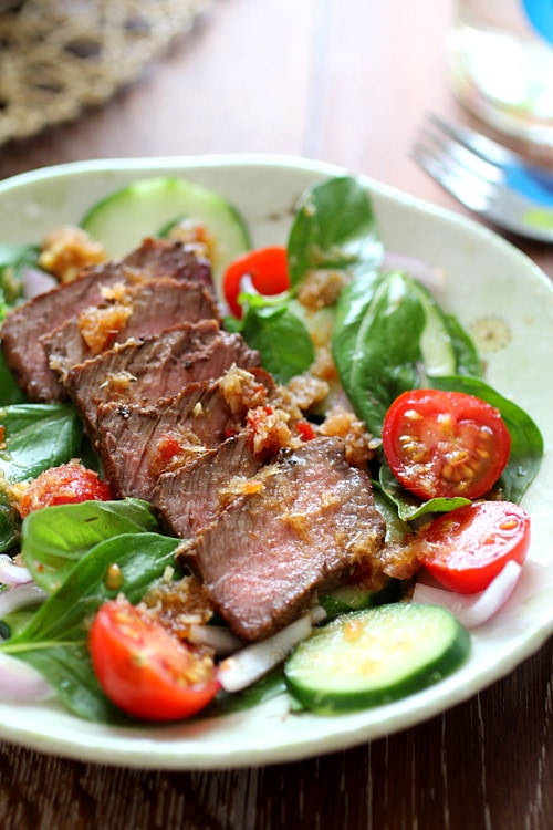 Healthy and easy Thai seared beef salad with basil leaves, tomatoes and a spicy Thai dressing.