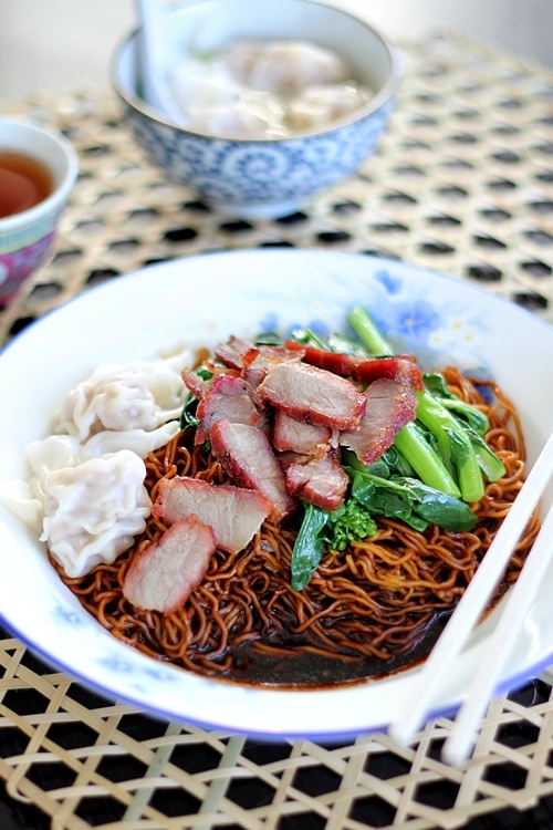 Wonton noodles with dark sauce on a plate.
