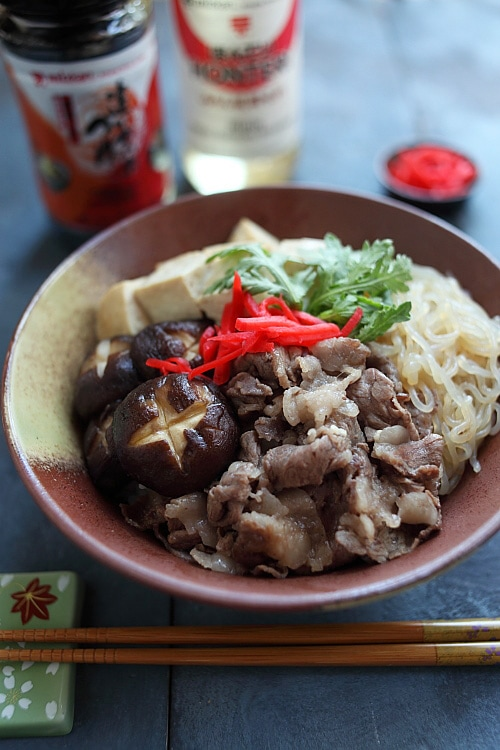 Closed up Japanese sukiyaki donburi rice bowl topped with beef slices, shitake mushrooms, tofu and shirataki noodles.