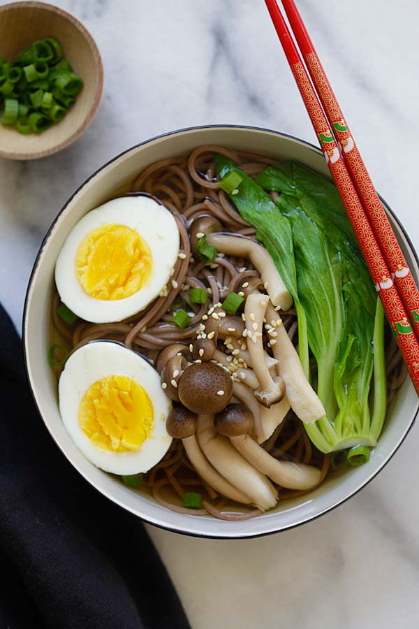 Quick and easy Japanese soba noodle soup with boiled eggs and Asian greens in a bowl.