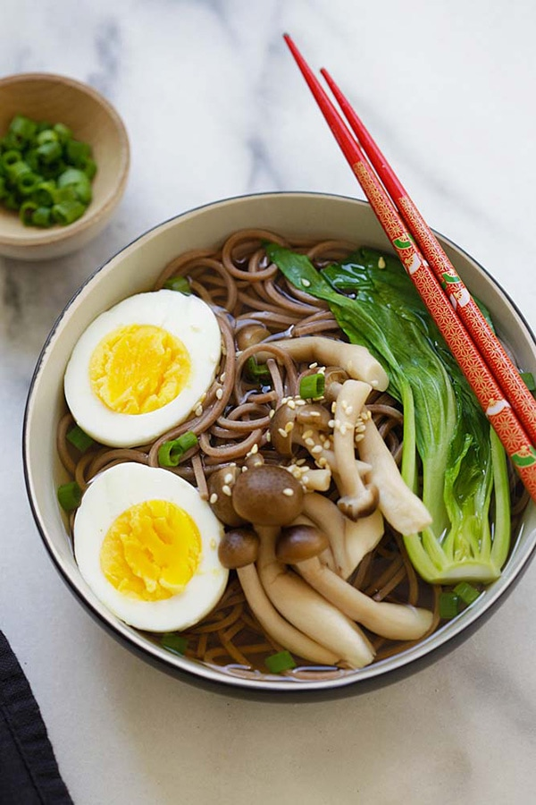 Healthy Japanese Soba noodle soup in a bowl with chopsticks.