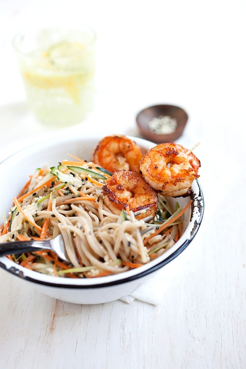 Chilled spicy sesame soba noodles with shrimp with a fork ready to serve.