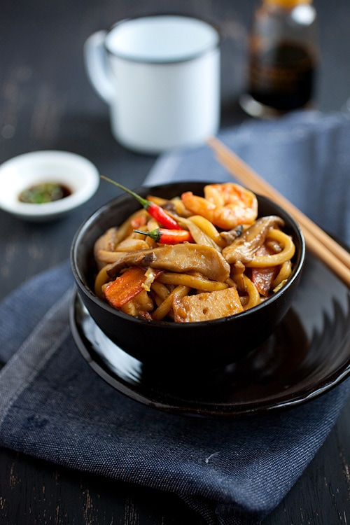 Easy homemade stir fry Malaysian style udon in brown Asian sauce served in a bowl.