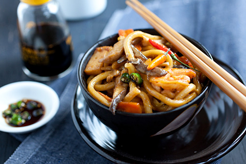 Quick and easy stir fried udon noodles in Asian brown thick sauce, served in a bowl with a pair of chopsticks.