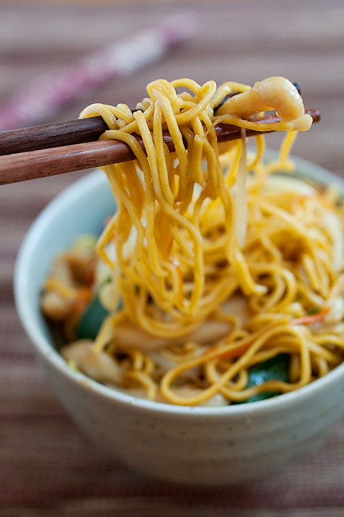 A pair of chopsticks holding up chicken chow mein with crispy noodles.