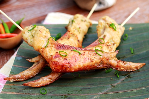 Easy and quick Southeast Asian chicken wings in skewers, placed on a banana leaf.