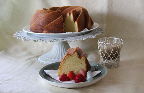 Homemade lemon cream cake sliced and placed on a plate, ready to serve.