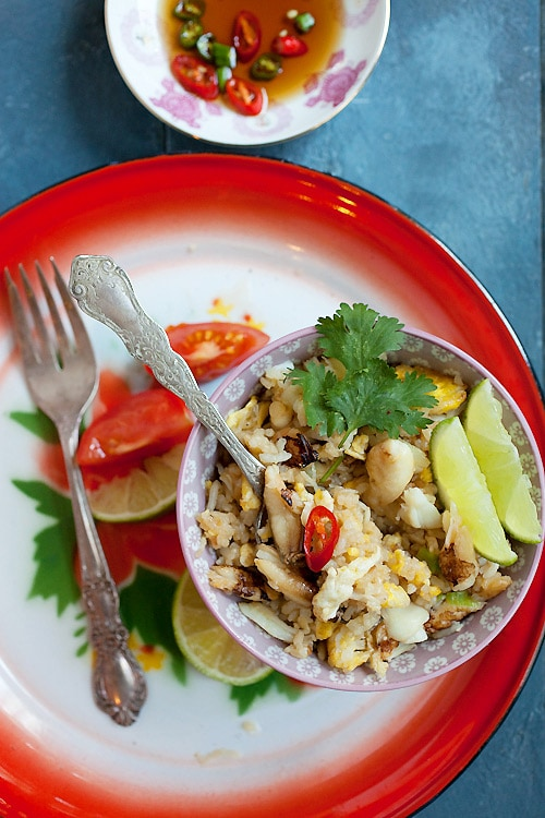 Easy and tasty Thai-style fried rice dish with rice, eggs, and crab meat with a side of sliced limes, and garnished with cilantro leaf.