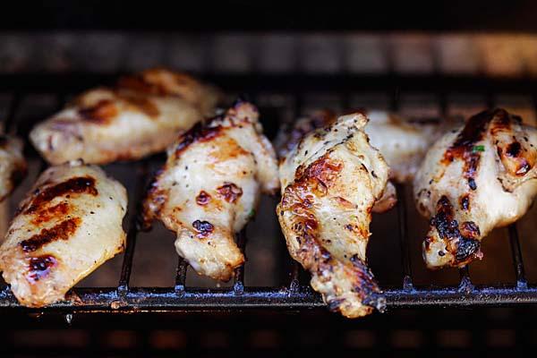 Lemongrass and fish sauce marinated lemongrass chicken wings on an outdoor grill.