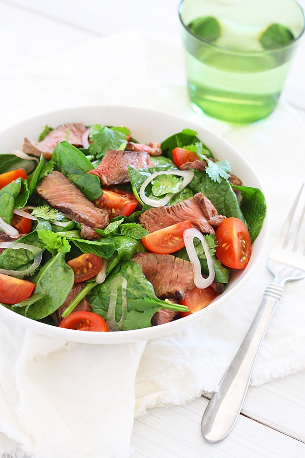 Thai Beef Salad with flavorful mint, cilantro and spinach in serving bowl.