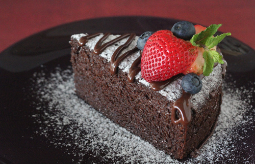 A piece of homemade no bake chocolate cake dusted with flour and decorated with berries.