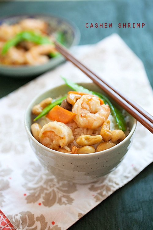 Easy and healthy Chinese stir-fry shrimp with cashew nuts in brown Chinese sauce, served on top of a bowl of steamed rice.