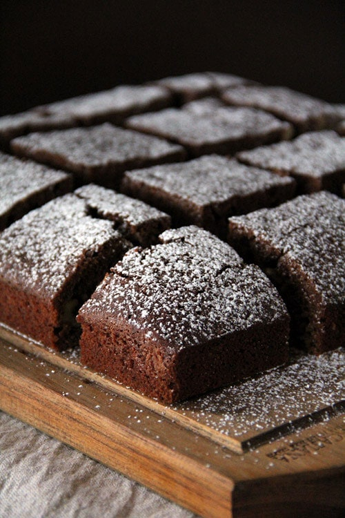 Easy homemade chocolate chip brownies sliced in square pieces, dusted with Confectioner's sugar.