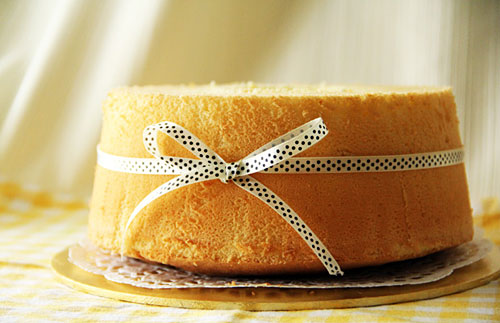 Perfect light and fluffy orange chiffon cake decorated with a ribbon, ready to serve.