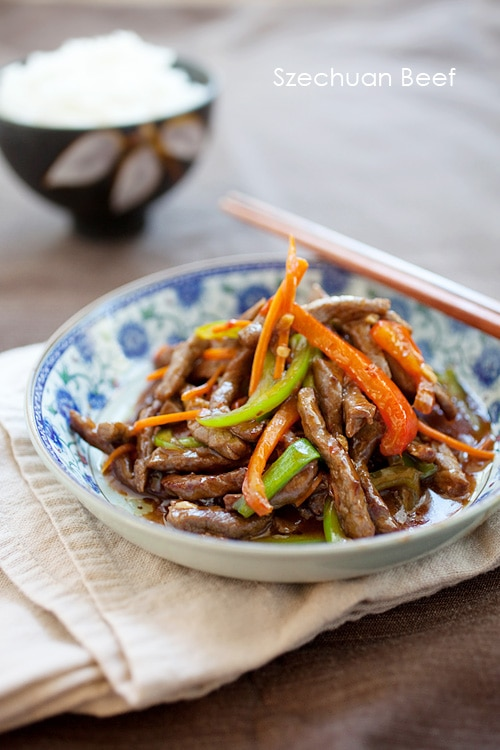 Easy and delicious Asian beef stir fry in mild spicy Szechuan sauce, served in a plate with a pair of chopsticks.