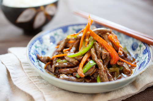 Chinese Szechuan beef stir fry in brown mild spicy sauce served in a plate.