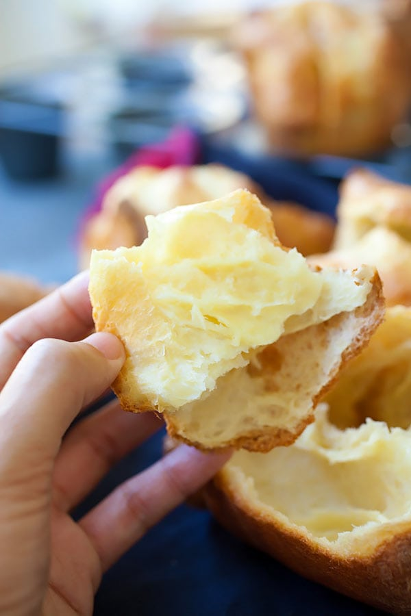 American popover recipe held in a hand, made with few ingredients and so easy to make.