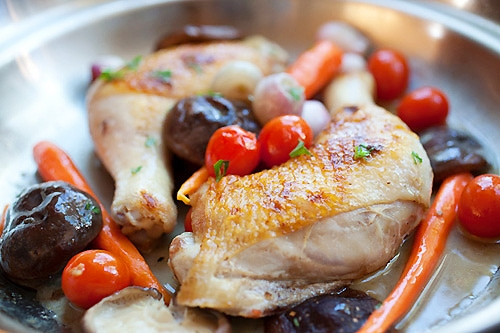 Braised chicken with carrot and mushroom in a skillet.