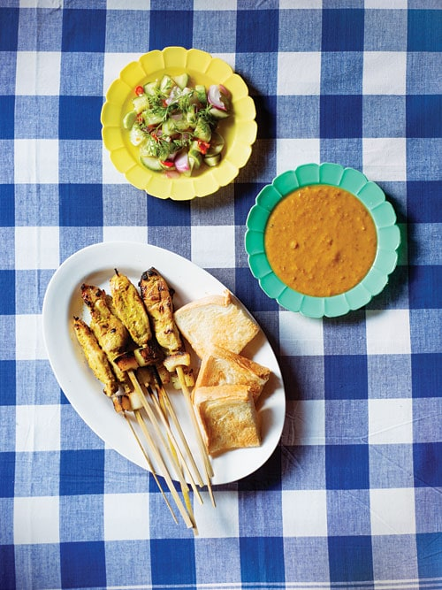 Easy homemade char grilled pork skewers, Thai Pork Satay, served in a plate with a side of Asian greens and satay peanut dipping sauce.