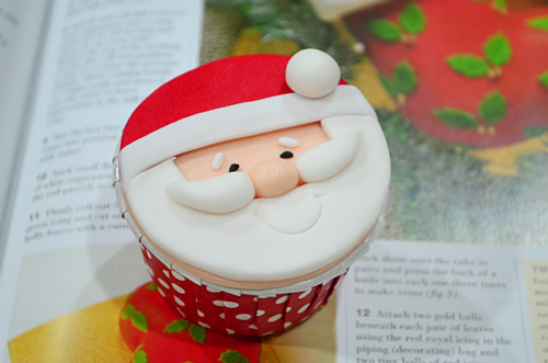 Easy homemade Christmas cupcakes with santa claus design, place on top of a magazine.
