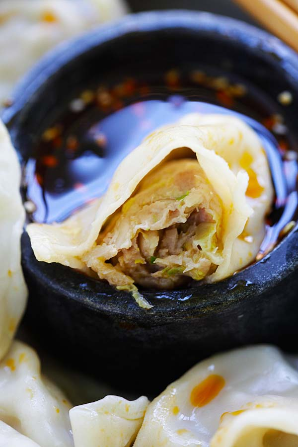 Close up homemade Chinese dumpling in half filled with pork, shrimp and napa cabbage.