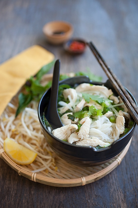 Vietnamese chicken pho recipe, with delicious rice noodles in a bowl and topped with herbs.