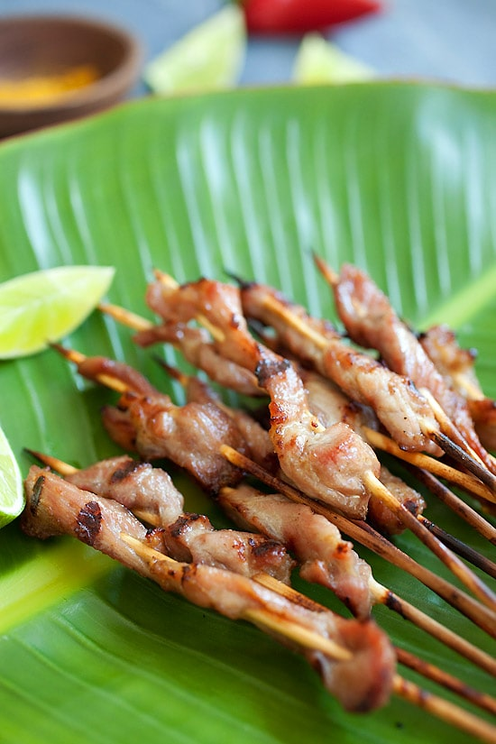 Easy Thai pork skewers with sweet coconut milk glaze on banana leave.