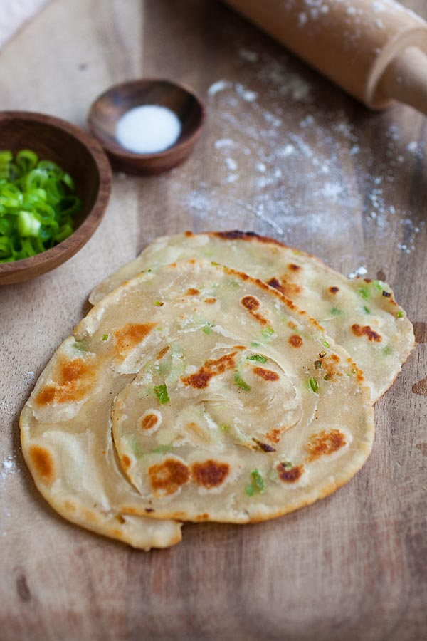 Chinese green onion pancake loaded with lots of scallion on wooden chopping board.