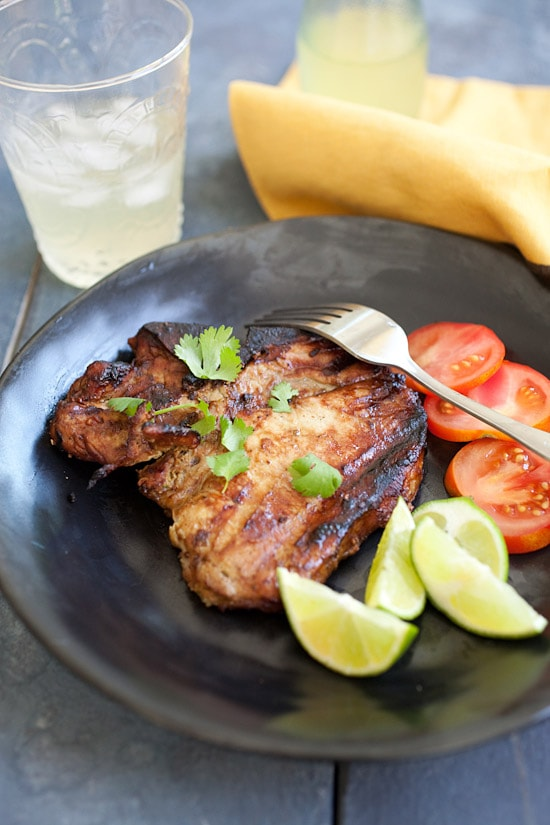 Juicy grilled pork chops served on a plate with sides of tomatoes and salad.