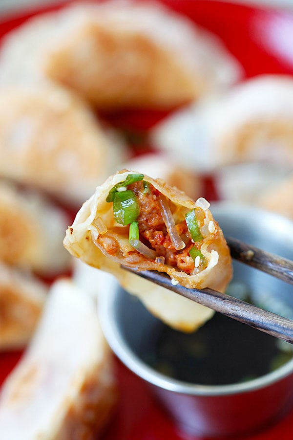 Juicy and delicious interior of Kimchi Dumplings picked with a pair of chopsticks.